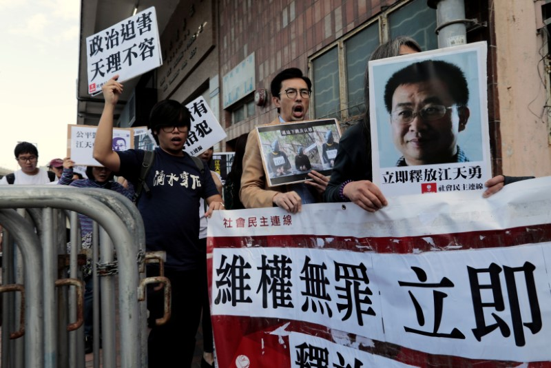 Pro-democracy demonstrators hold up portraits of Chinese disbarred lawyer Jiang Tianyong, demanding his release, during a demonstration outside the Chinese liaison office in Hong Kong, China December 23, 2016. Photo: Reuters/Tyrone Siu