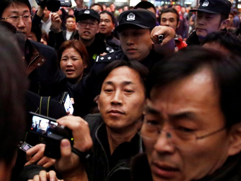 North Korean national Ri Jong-chol (center) is surrounded by media after his arrival at Beijing airport. Photo: Reuters/Thomas Peter