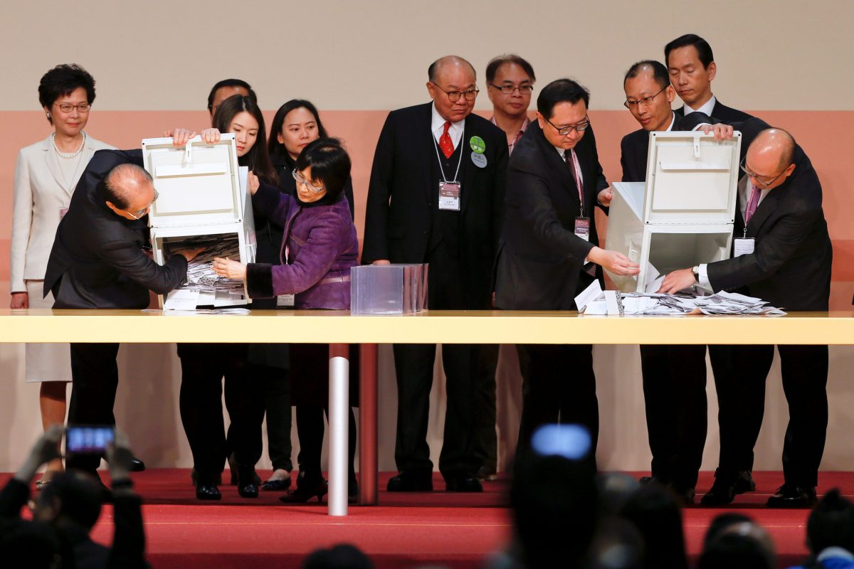 Candidates Woo Kwok-hing and Carrie Lam look on as officials open ballot boxes.   Photo: Reuters/Bobby Yip