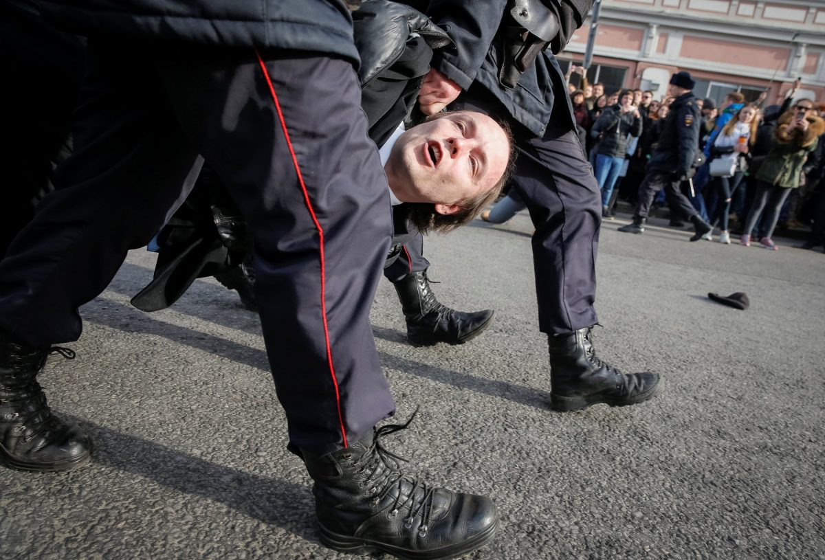 Law enforcement officers detain an opposition supporter during a rally in Moscow.  REUTERS/Maxim Shemetov