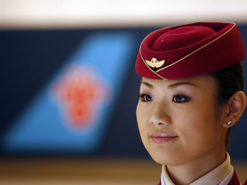 A China Southern Airlines flight attendant stands in front of the company's logo. Photo: Reuters, Nicky Loh