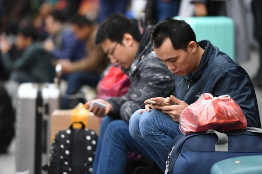 Chinese passengers who go back home for the Chinese Lunar New Year use their smartphones to surf the Internet. Photo: Imaginechian/Hu Yan
