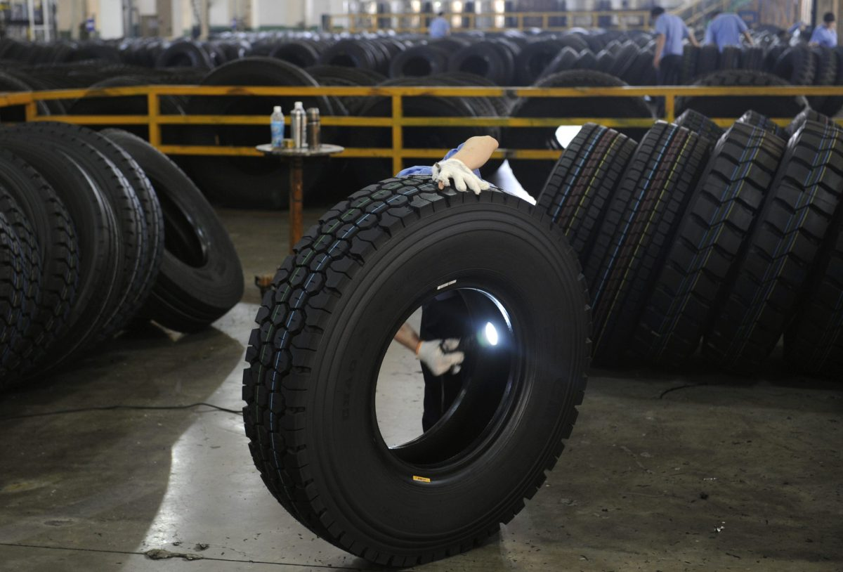 An employee inspects the interior of a newly-made tire with a flashlight at a tyre factory in Hangzhou, Zhejiang province. Photo: Reuters, Lang Lang