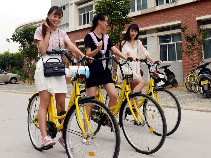 Students pose for pictures as they use ofo sharing bicycles at a campus in Zhengzhou, China, Photo: Reuters via China Daily