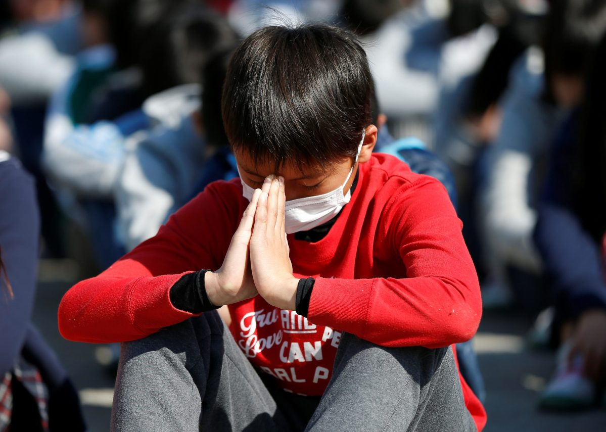 A student prays as he observes a moment of silence for the victims of the March 11, 2011 earthquake and tsunami during an earthquake simulation exercise at an elementary school in Tokyo, Japan March 10, 2017, a day before the six-year anniversary of the March 11, 2011 earthquake and tsunami disaster that killed thousands and set off a nuclear crisis. Reuters/Issei Kato
