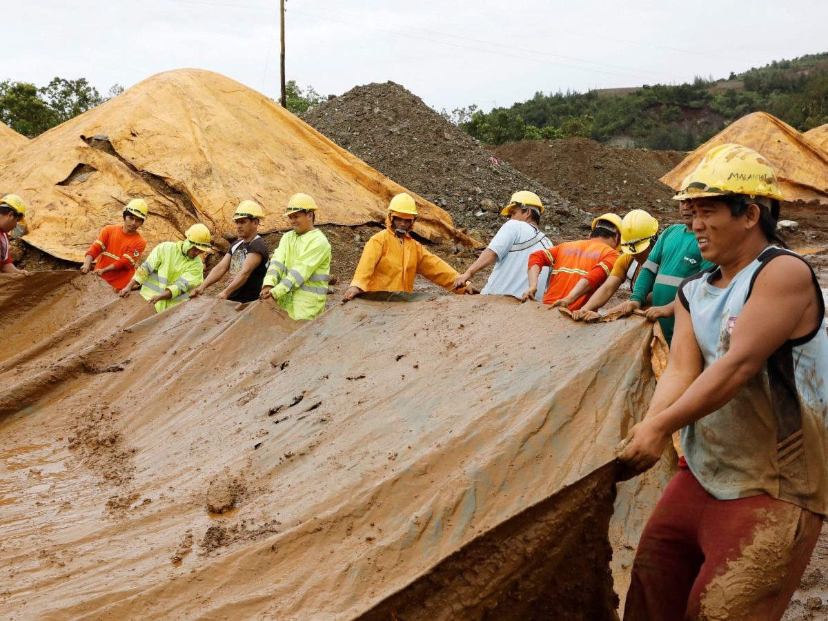 Workers cover a stockpile of nickel ore minerals with a tarp to avoid moisture in Tubay, Agusan del Sur, in southern Philippines February 16, 2017. Photo: Reuters / Erik De Castro