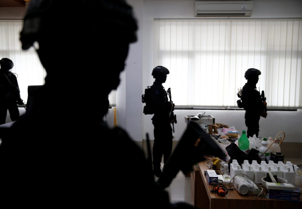 Indonesian anti-terror police from Detachment 88 stand guard near explosive materials and other evidence confiscated in raids on suspected militants during a media briefing at police headquarters in Jakarta, Indonesia, November 30, 2016. Picture taken November 30, 2016. REUTERS/Beawiharta - RTX2WABJ