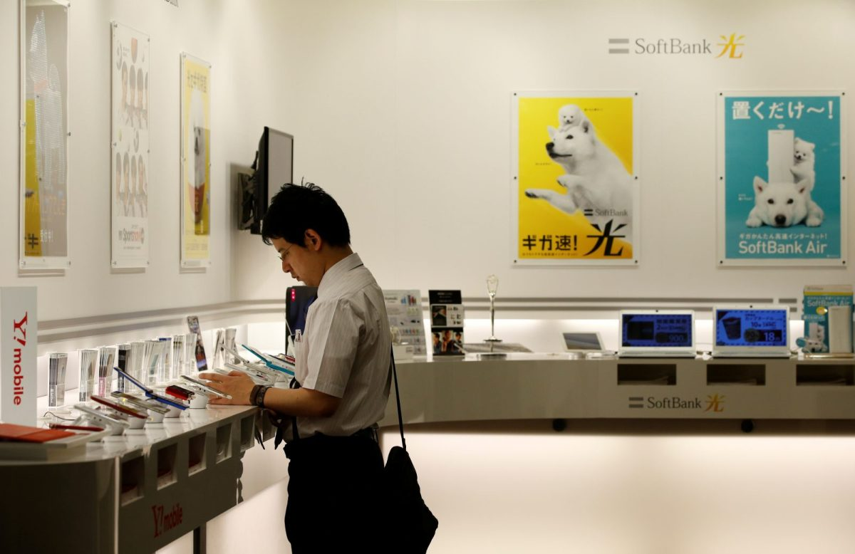 A man looks at mobile phones at the Softbank's headquarters in Tokyo. Photo: Reuters, Toru Hanai