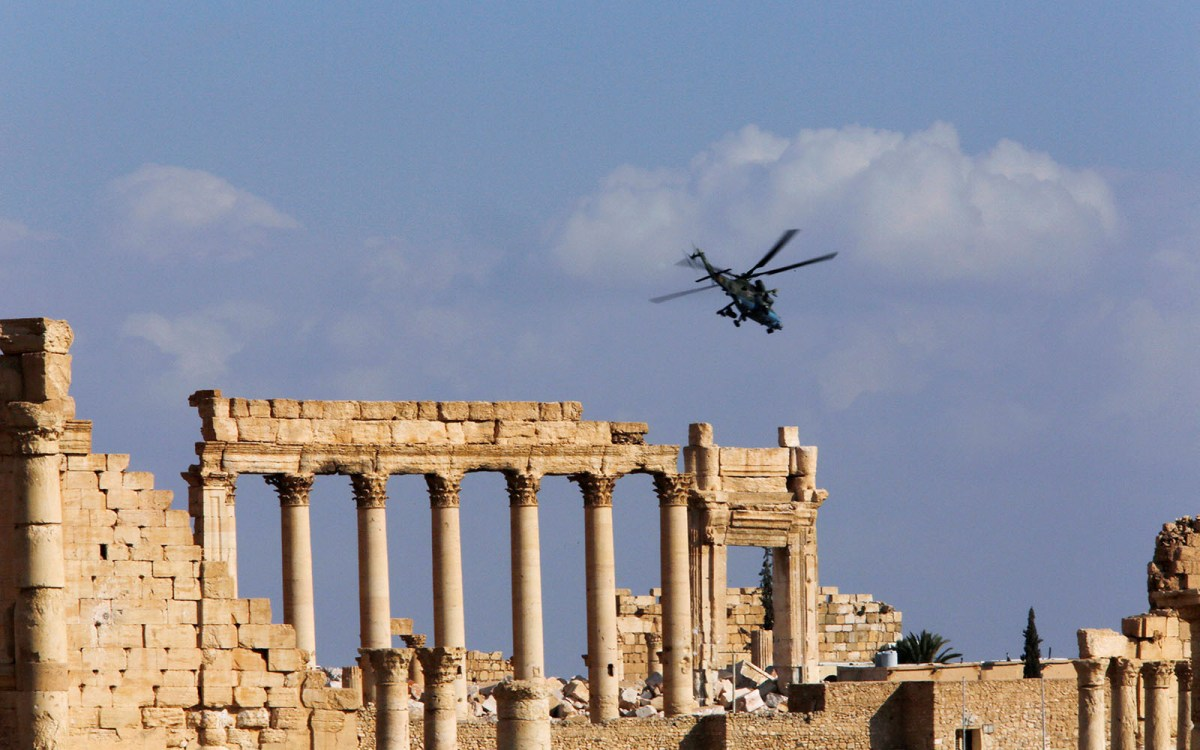 A Russian helicopter flies over the Temple of Bel in the historic city of Palmyra, Syria. Photo: Reuters