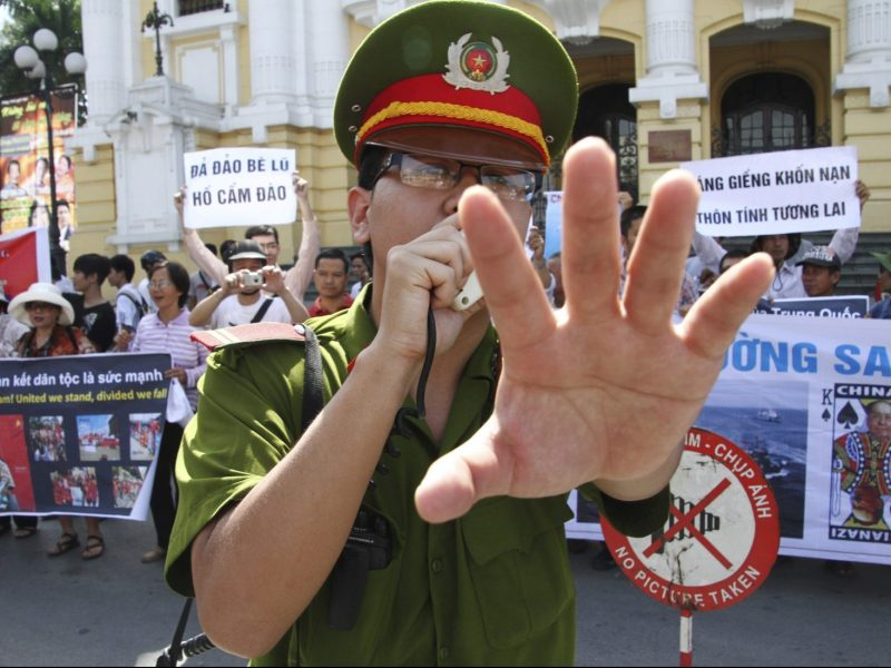 A policeman blocks photographers from taking pictures during an anti-China protest in front of the Opera House in Hanoi in a file photo. Photo: Reuters/Nguyen Lan Thang