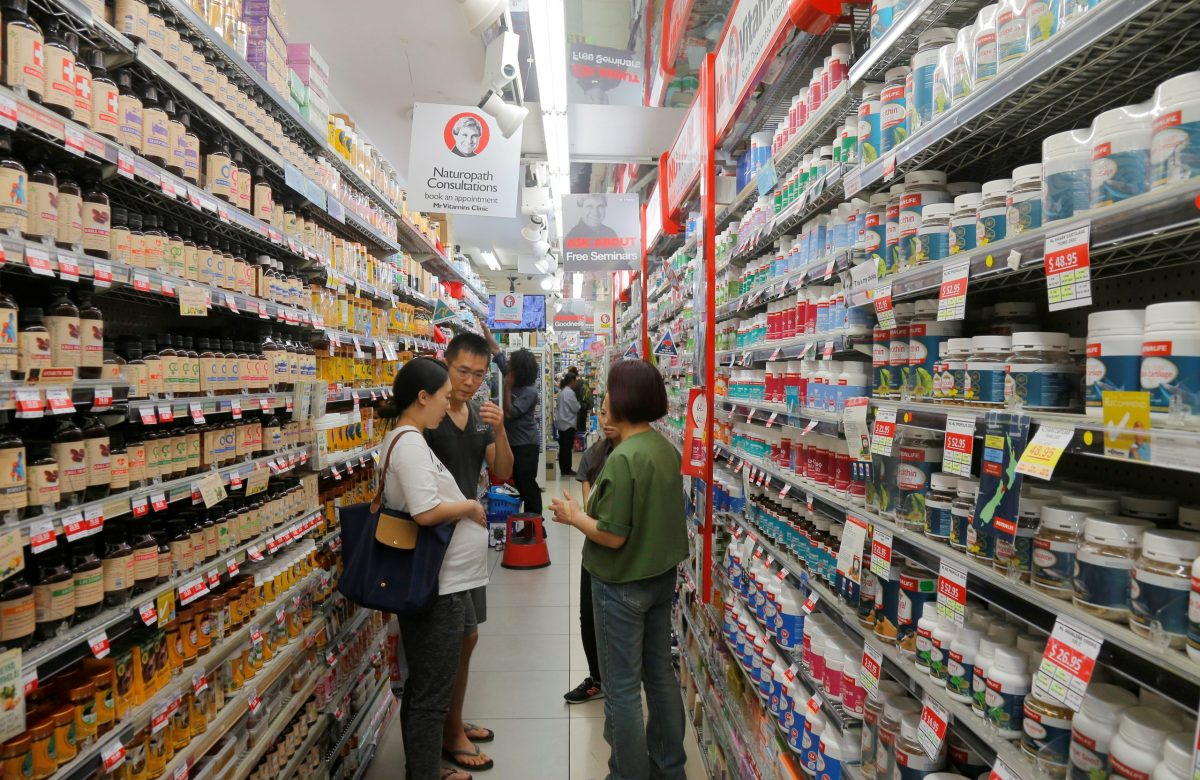 Shoppers browse for health products in an aisle stocked with vitamin supplements. Photo: Reuters, Jason Reed