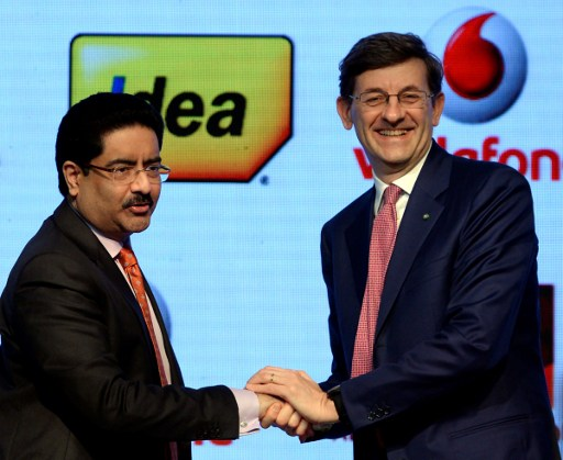 Vodafone Group CEO Vittorio Colao (R) shakes hand with chairman of India's Aditya Birla Group Kumar Mangalam Birla. Photo: AFP, Punit Paranjpe