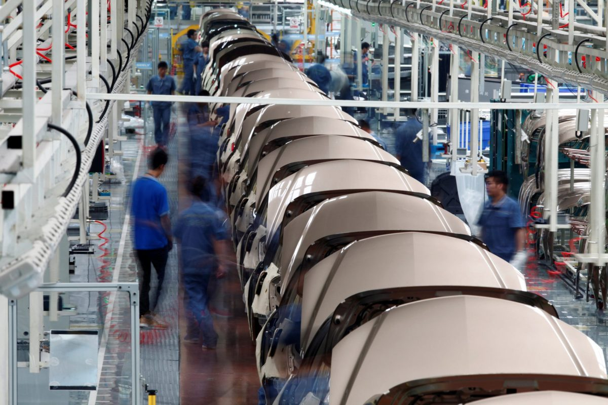 Employees work along a Geely Automobile assembly line in Cixi, Zhejiang province.   Photo: Reuters/Carlos Barria
