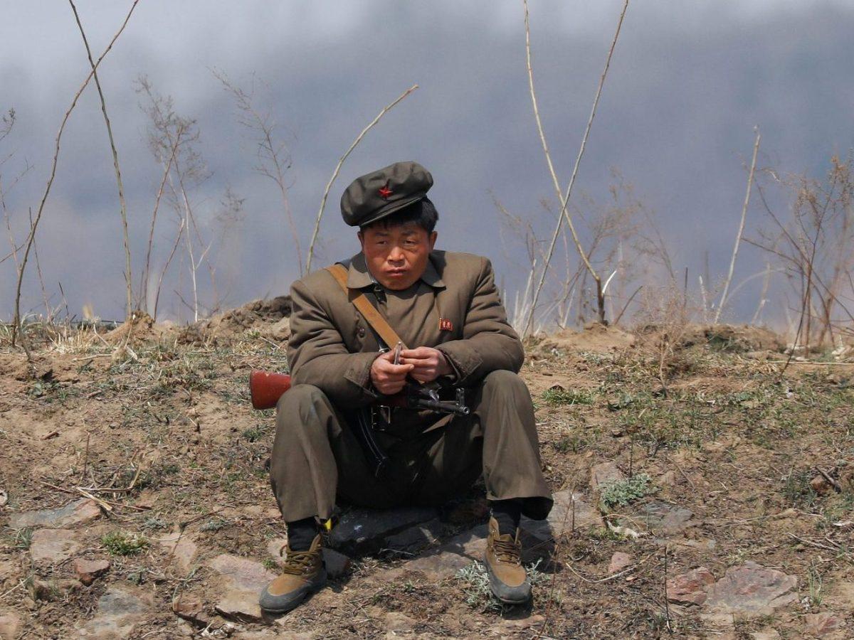 A North Korean soldier sits on a bank of the Yalu River just north of Sinuiju, North Korea, on April 2, 2017. Photo: Reuters / Damir Sagolj