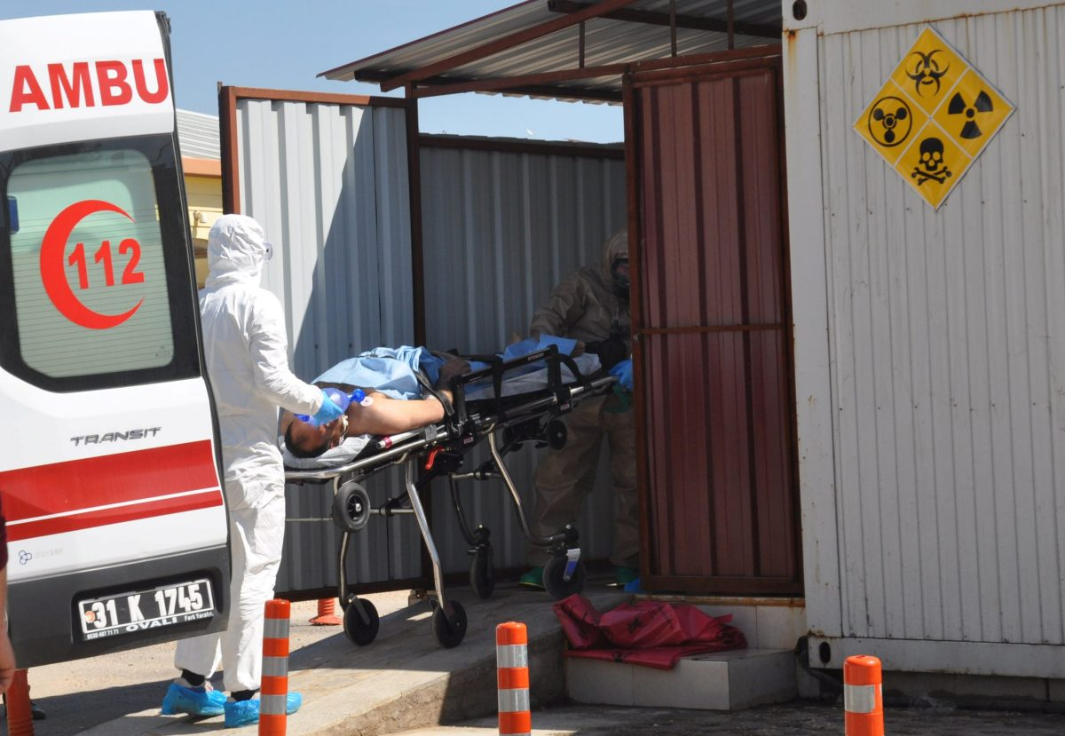 A Syrian man from Idlib is carried by Turkish medics wearing chemical protective suits to a hospital in the border town of Reyhanli in Hatay province. Photo: Ferhat Dervisoglu / Dogan News Agency via Reuters