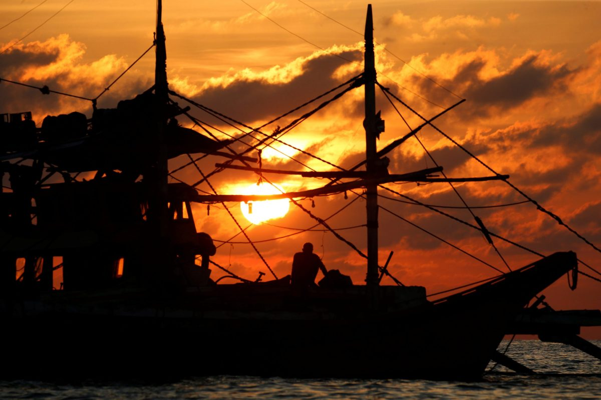 A Philippine fisherman sits on his boat during sunset at the disputed Scarborough Shoal. Photo: Reuters/Erik De Castro