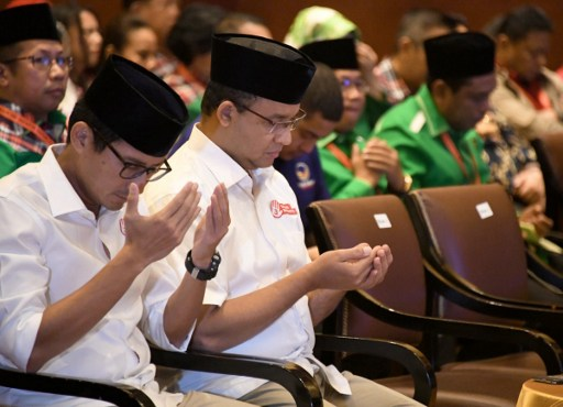 Anies Rasyid Baswedan (2L) and his running mate Sandiaga Salahuddin Uno (L) pray during an event held by the election commission. Photo AFP PHOTO, Goh Chai Hin