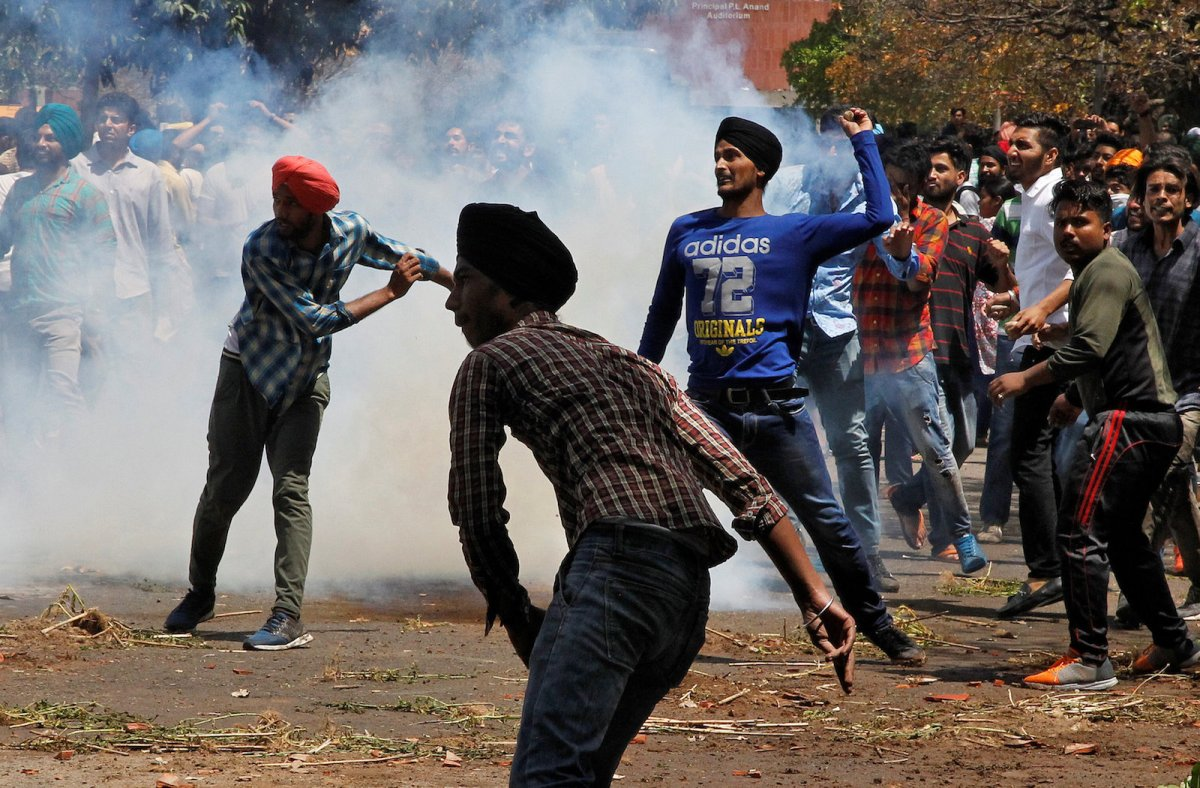 Police and paramilitary forces in parts of India have been accused of rights abuses up to and including extrajudicial killings, often in non-Hindu areas. Here students hurl stones toward police during a protest in Chandigarh on April 11, 2017. Photo: Reuters/Ajay Verma
