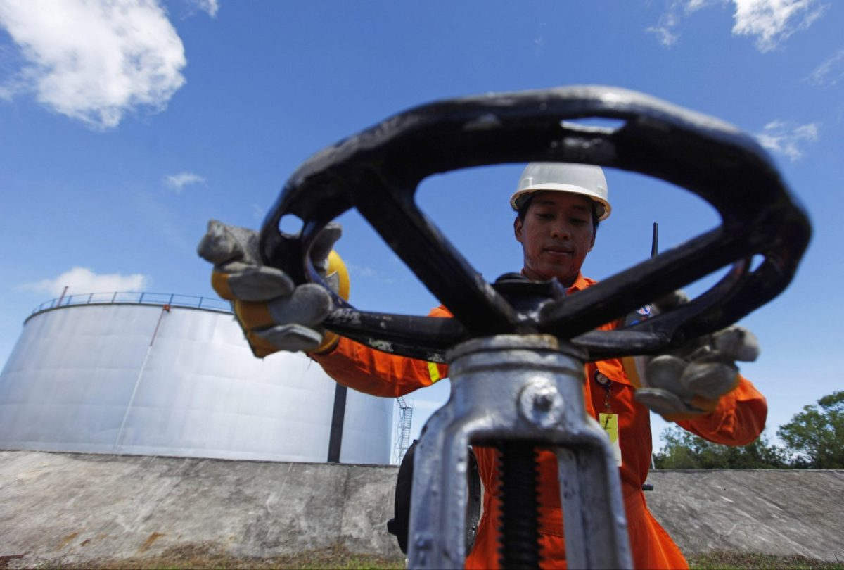 An Indoensian oil worker opens a gauge near crude oil tanks on Bunyu island, Indonesia's East Kalimantan province. Photo: Reuters/Beawiharta