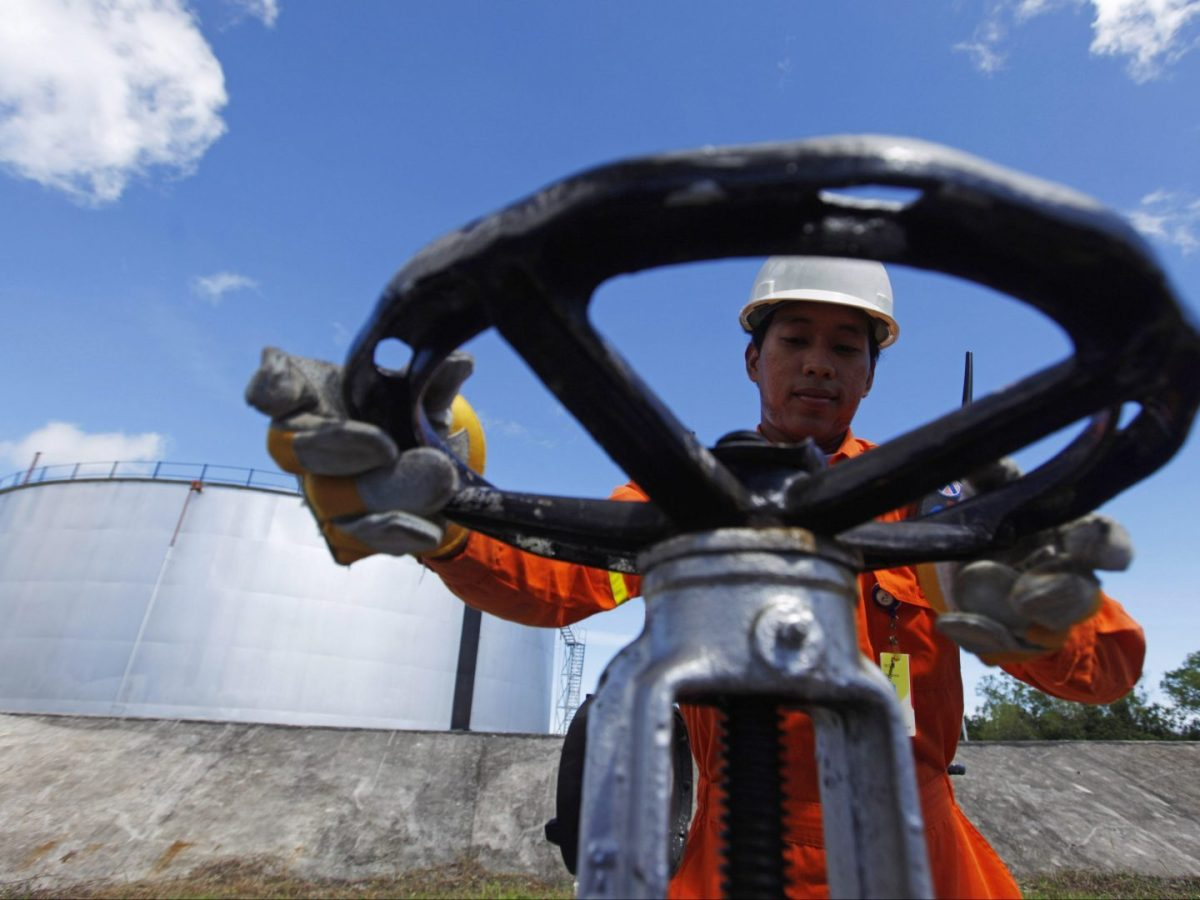An Indoensian oil worker opens a gauge near crude oil tanks on Bunyu island, Indonesia's East Kalimantan province. Photo: Reuters/Beawiharta