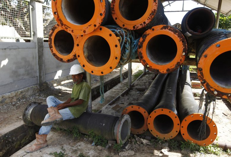 A PT Pertamina worker sits under pipes as he rests near crude oil tanks at Bunyu island, Indonesia's East Kalimantan province February 8, 2011. Pertamina has said it expects crude and condensate production of 132,000 barrels per day for this year, up just 1 percent from last year, though the former OPEC member country has often missed production targets because of declining output at ageing fields, Pertamina's director of investment and risk management Ferederick Siahaan said last month. REUTERS/Beawiharta (INDONESIA - Tags: ENERGY BUSINESS) - RTXXLW8