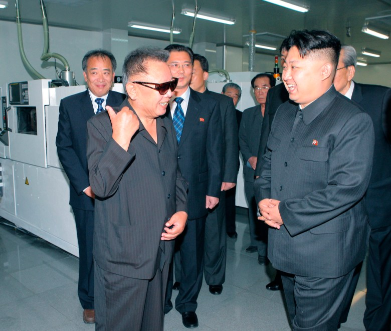 North Korean leader Kim Jong-il (front left) and his son Kim Jong-un talk as they visit Mokran Video Company in Pyongyang in this undated image. Heir apparent Kim Jong-un's slicked-back, high-sided haircut is a fashion hit in Pyongyang where young men are apparently queueing up for a similar cut. Photo: KCNA via Reuters