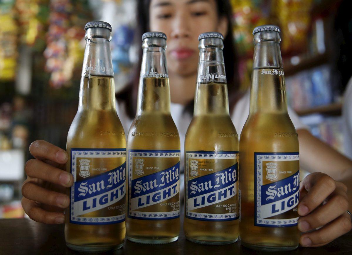 A storekeeper displays San Mig Light beer, a product of San Miguel brewery. Photo: Reuters/ Erik de Castro