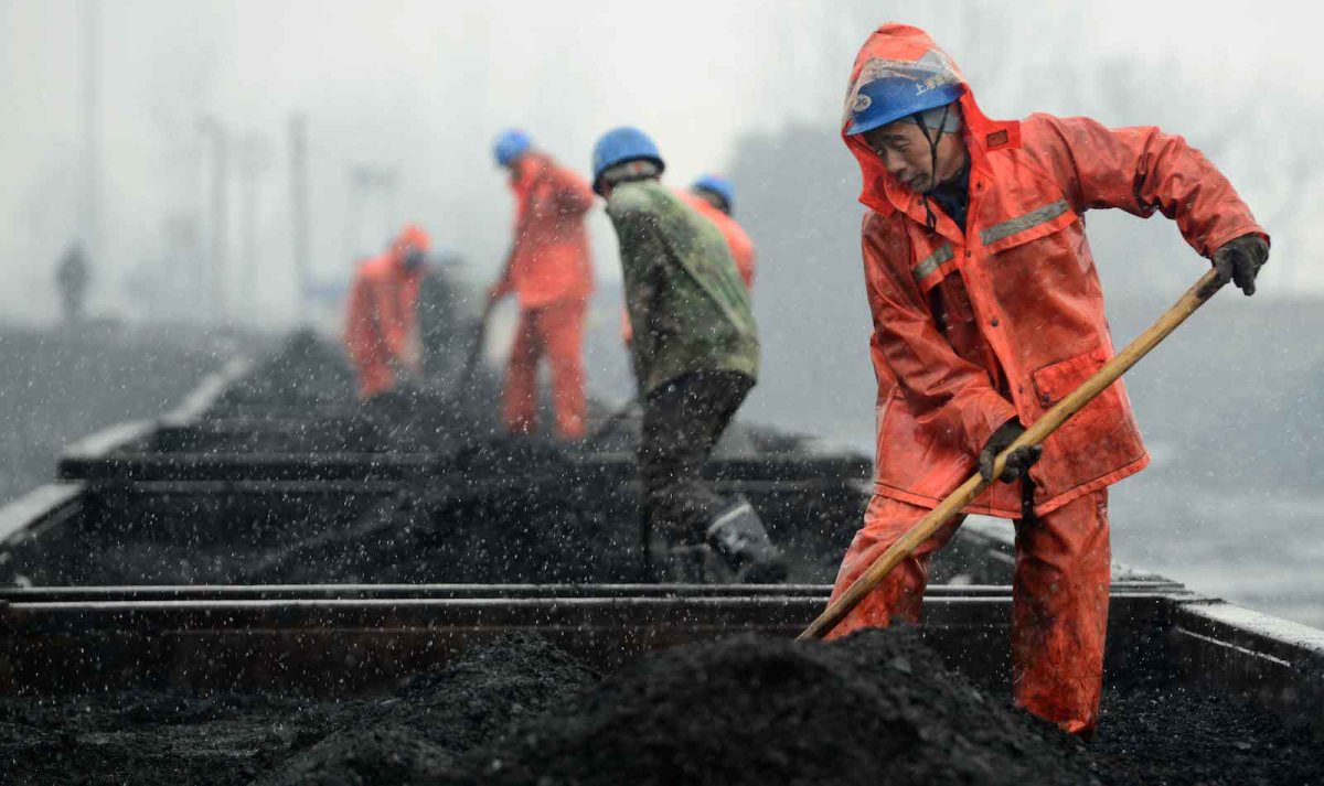 Chinese workers level coal destined for one of China's electricity generating plants. Photo: AFP