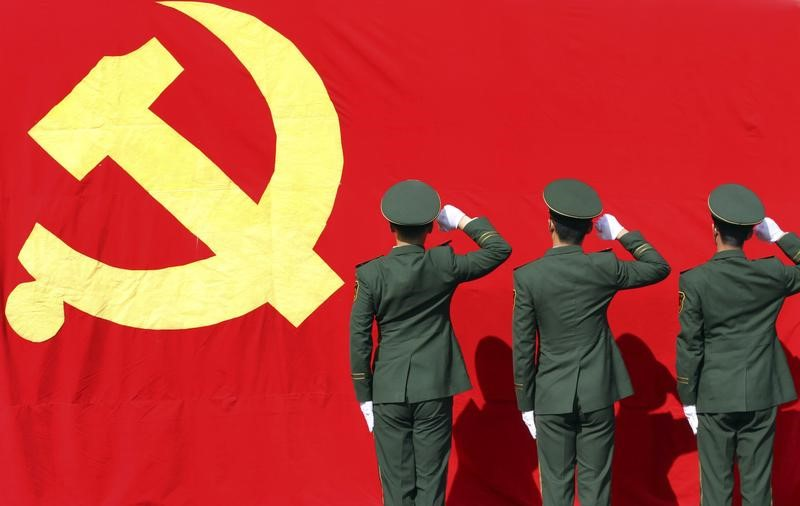 Paramilitary police raise fists to the Communist Party of China flag. Photo: Reuters/China Daily
