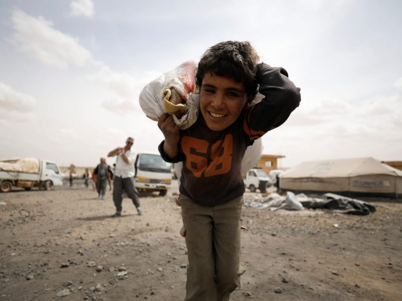 An internally displaced Syrian boy from Raqqa city carries a bag of goods inside a camp in Ain Issa, Raqqa Governorate, Syria, on May 2, 2017. Photo: Reuters / Rodi Said