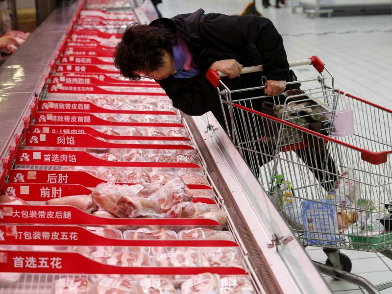 A customer chooses a meat product at Sun Art Retail Group's Auchan hypermarket store in Beijing, China, on November 9, 2015. Photo: Reuters/Kim Kyung-Hoon