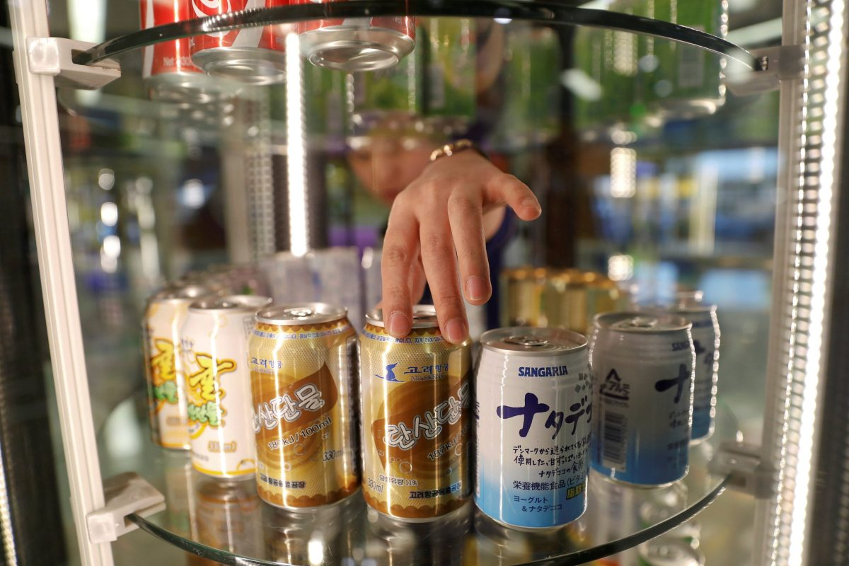 A vendor adjusts cans of soft drinks made by Air Koryo, at the airport in Pyongyang. Photo: Reuters/Damir Sagolj