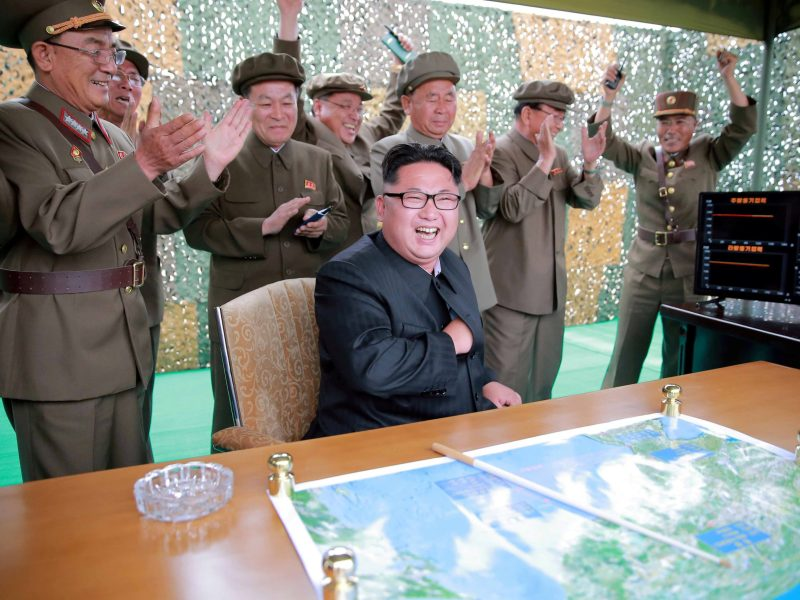 Kim Jong-un reacts with some of his rocket scientists during a test launch of ground-to-ground medium long-range ballistic rocket Hwasong-10 in the undated picture. Photo: KCNA via Reuters