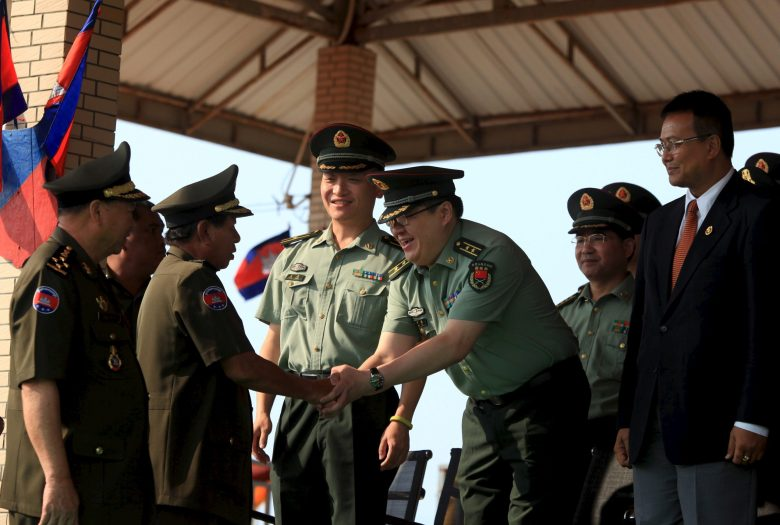 Cambodia's Deputy Prime Minister and Defence Minister Tea Banh (2nd L) shakes hands with a Chinese army advisor during a graduation ceremony at Army Institute in Kampong Speu province March 12, 2015. When Defence Minister Tea Banh addressed graduates last month at Cambodia's prestigious Army Institute, he directed his thanks to the guests who made it all possible: a group of crisply dressed officers from China's People's Liberation Army (PLA). Military aid, alongside arms sales and billions of dollars of investment, have strengthened China's ties with Cambodia, and analysts see it as part of a push to extend regional influence, including in the disputed South China Sea. Picture taken March 12, 2015. REUTERS/Samrang PringREUTERS/Samrang Pring - RTR4VUK6