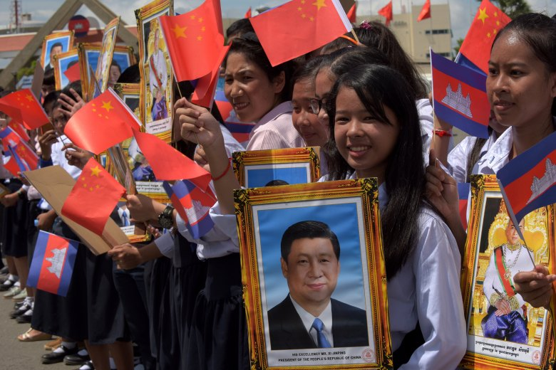 Cambodian students hold portraits of Chinese President Xi Jinping (C) and Cambodian King Norodom Sihamoni (R) during Xi's arrival at Phnom Penh international airport on October 13, 2016.Xi is in Cambodia on a two-day state visit. / AFP PHOTO / TANG CHHIN SOTHY