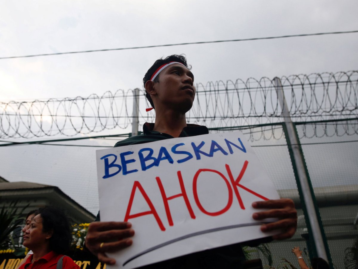"""A man holds a sign that says """"Free Ahok"""" during a protest by supporters of Jakarta governor Basuki Tjahaja Purnama outside Cipinang Prison, where he was taken after his conviction of blasphemy in Jakarta on May 9, 2017.   Photo: Reuters/Darren Whiteside"""
