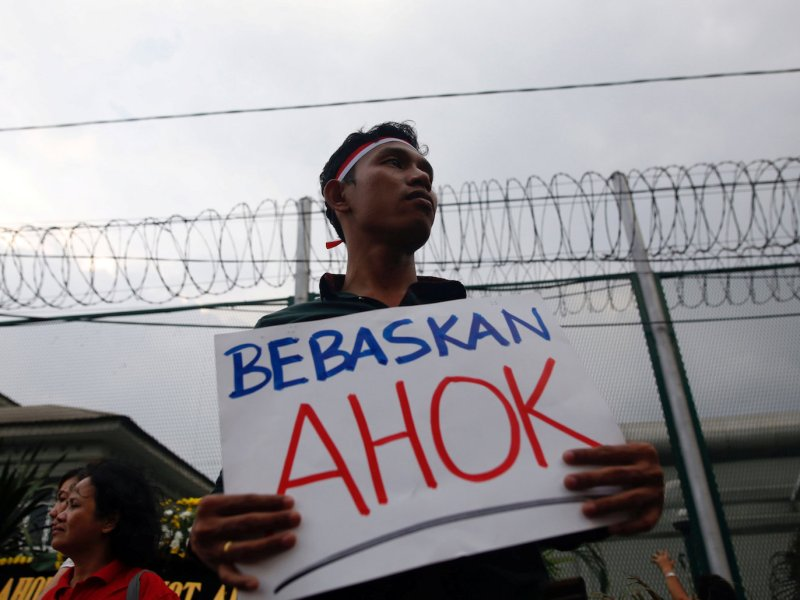 "A man holds a sign that says ""Free Ahok"" during a protest by supporters of Jakarta governor Basuki Tjahaja Purnama outside Cipinang Prison, where he was taken after his conviction of blasphemy in Jakarta on May 9, 2017.   Photo: Reuters/Darren Whiteside"