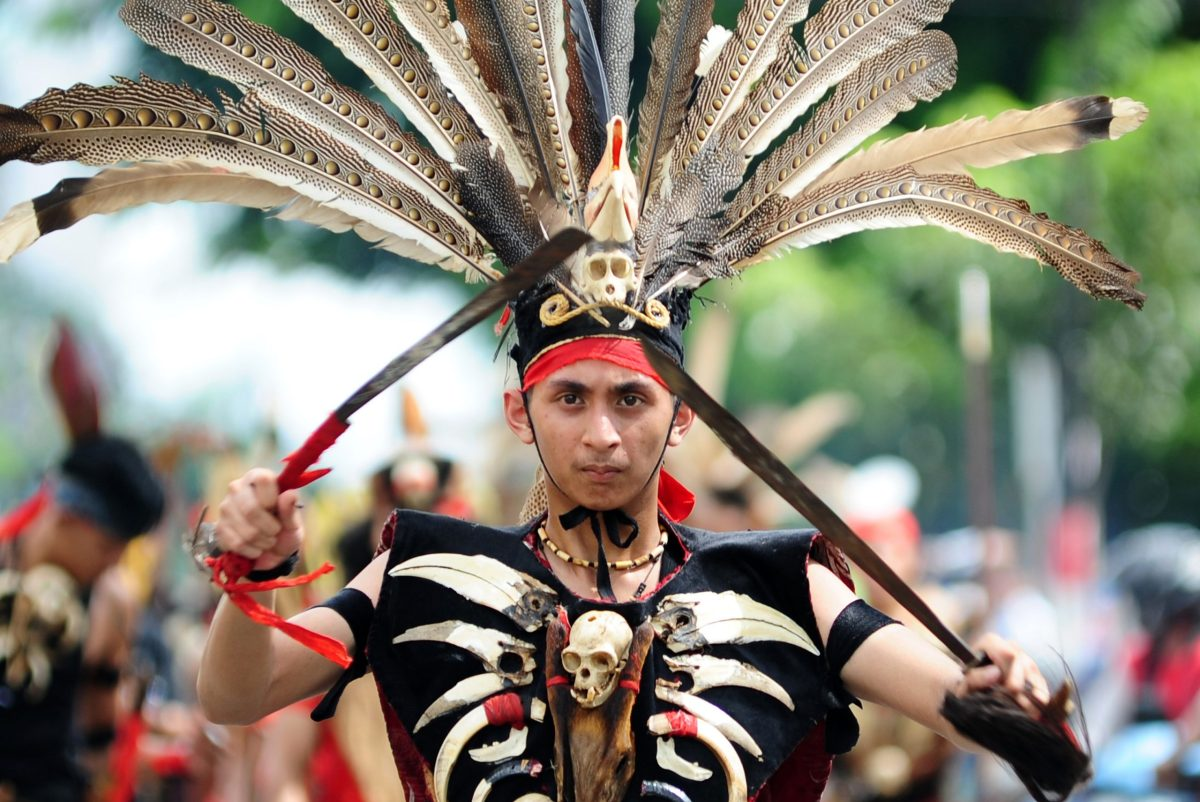 A Dayak tribe member holds a traditional mandau sword while wearing traditional clothing adorned with animal skull necklaces as he takes part in an annual festival in Pontianak, West Kalimantan province, on May 20, 2017. Photo: AFP