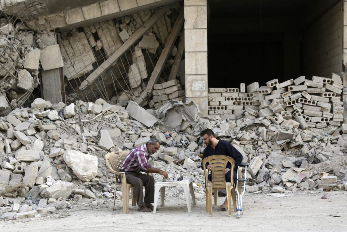 Men play chess in front of a damaged building in Maaret al-Naaman, Idlib province. Photo: Reuters / Khalil Ashawi