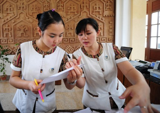 Hotel staff in Sanya, in southern China's tropical Hainan province where tourism is key to the island's economy.  Photo: AFP / Frederic J. Brown