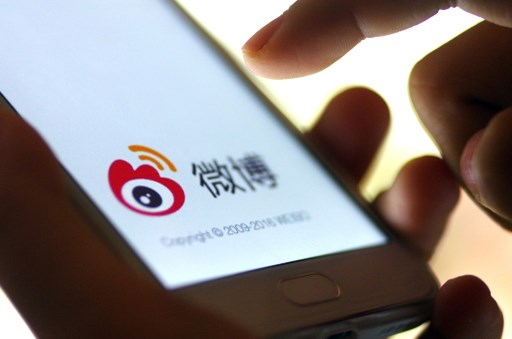 A mobile phone user uses  Twitter-like microblog Weibo of Chinese Internet portal Sina. Photo: AFP