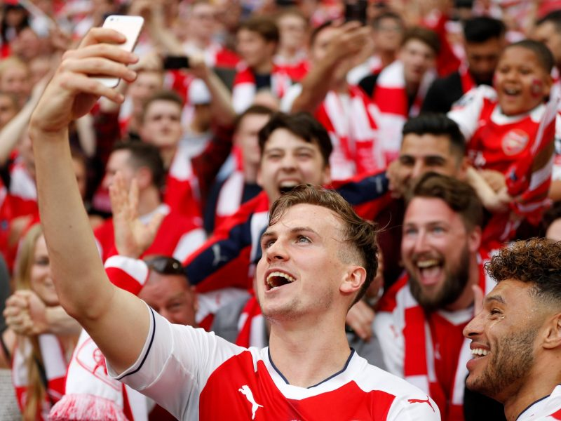 Arsenal's Rob Holding and Alex Oxlade-Chamberlain pose for a selfie with fans at the end of their FA Cup Final win over Chelsea.  Photo: Reuters / John Sibley