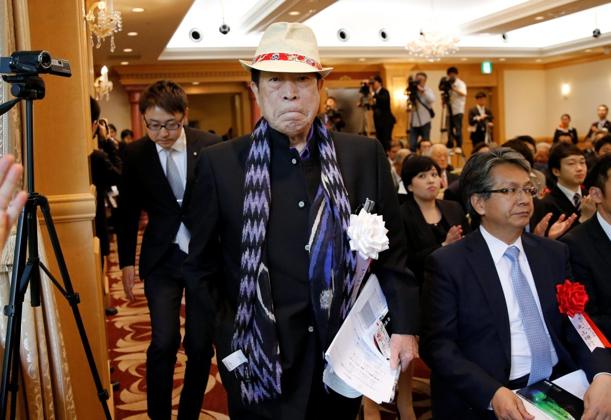 APA Group CEO Toshio Motoya, holding his book that denies the 1937 massacre by Japanese troops in the Chinese city of Nanjing ever took place, arrives at a news conference in Tokyo on June 2, 2017.  Image: Reuters