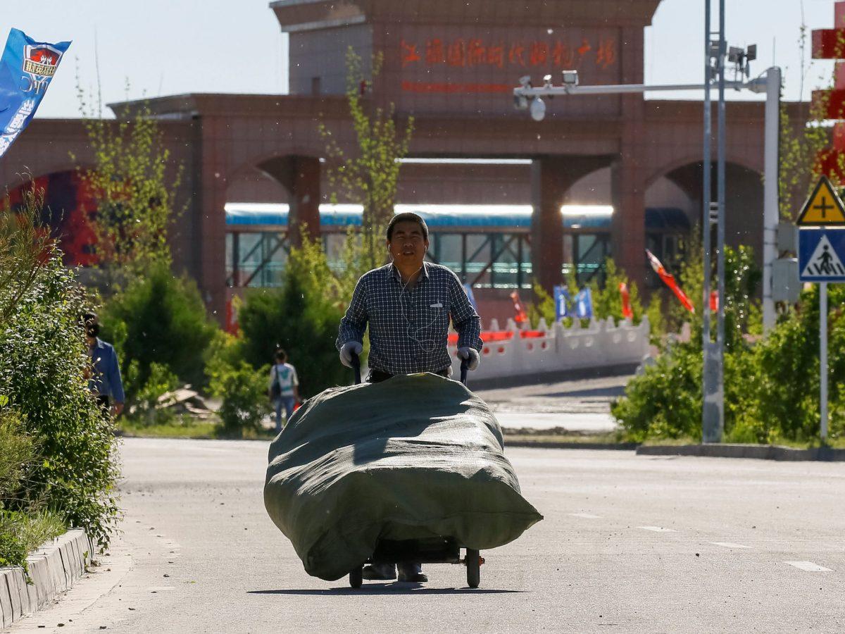 A man walks with a cart at Chinese part of the China-Kazakhstan Horgos International Border Cooperation Center (ICBC), in Horgos, China May 12, 2017. REUTERS/Shamil Zhumatov