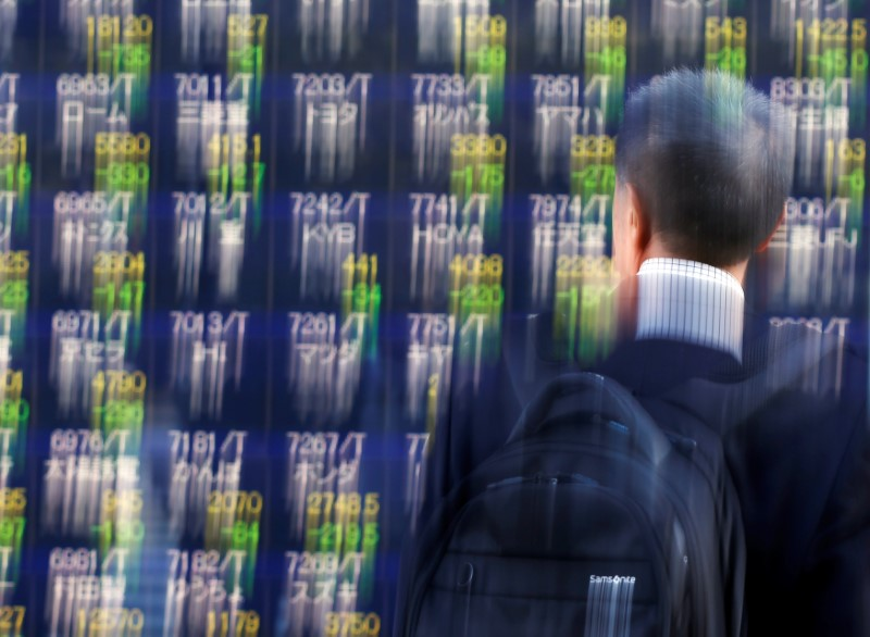 A man looks at an electronic stock quotation board outside a brokerage in Tokyo, Japan, on November 9, 2016. Photo Reuters / Issei Kato