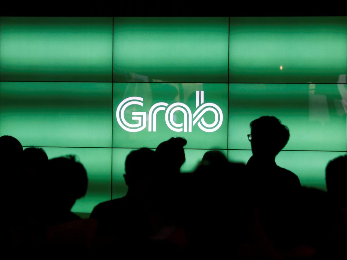 People wait for the start of Grab's fifth anniversary news conference in Singapore. Photo: Reuters/Edgar Su