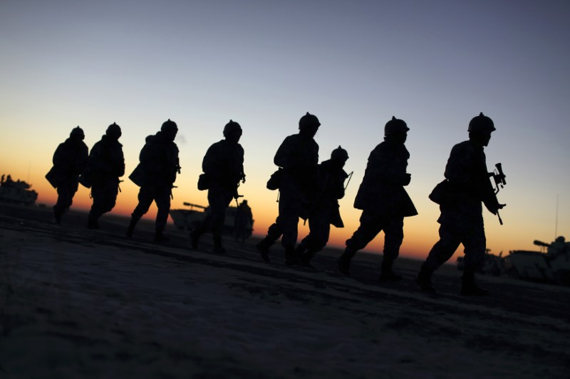 Soldiers of the People's Liberation Army (PLA) Marine Corps march during a military drill as the sun rises at a military base in Taonan, Jilin province. Photo: Reuters/China Daily