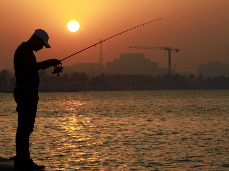 A man fishes as the sun sets in Doha, Qatar, June 15, 2017. Photo: Reuters / Naseem Zeitoon