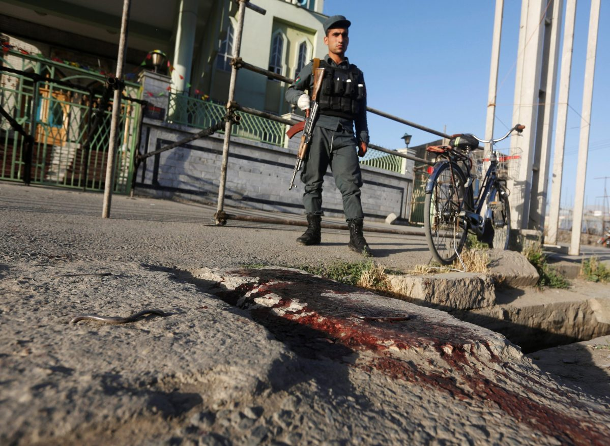 An Afghan policeman looks at bloodstains of victims outside a mosque where a suicide bomber detonated a bomb in Kabul in June. Photo: Reuters / Omar Sobhani