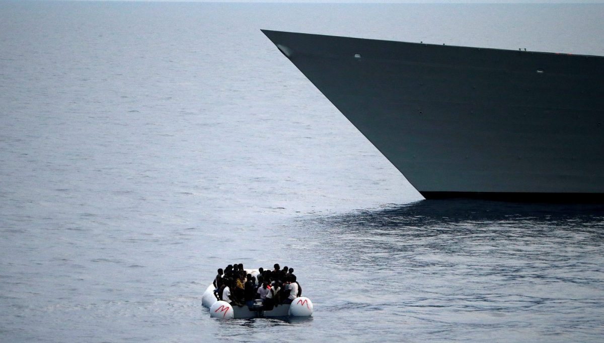 Migrants on a dinghy wait to be rescued  as Spanish frigate Canarias approaches in the Mediterranean sea. Photo:  Reuters/Stefano Rellandini